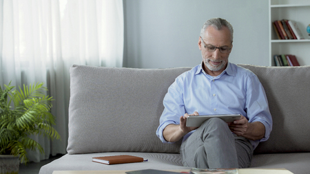 Smiling adult person sitting on couch and viewing family photos on tablet