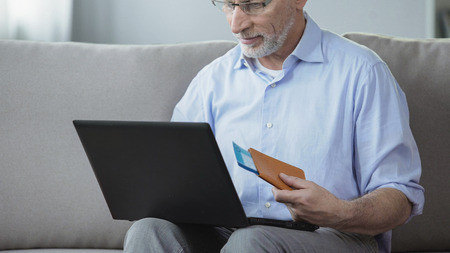 Old person viewing photos of resort town, booking hotel room on laptop at home