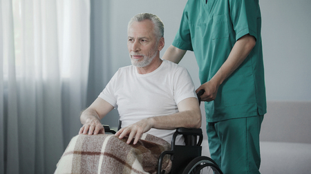 Worker of rehabilitation center supporting old ill man, advising not to give up