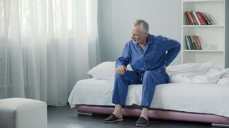 Hoger mannetje die aan scherpe rugpijn, zieke lijden die van bed, ochtend opstaan
