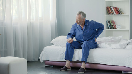 Senior male suffering sharp back pain, sick person getting up from bed, morning Banque d'images
