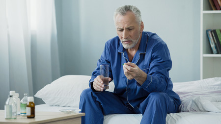 Male pensioner taking daily vitamin complex to maintain genitourinary system