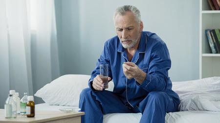 Männlicher Pensionär, der täglichen Vitaminkomplex nimmt, um Urogenitalsystem beizubehalten