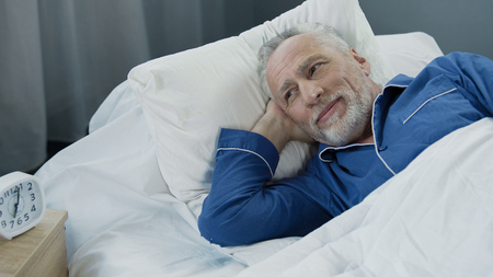 Senior male waking up and smiling after comfortable healthy sleep, health care