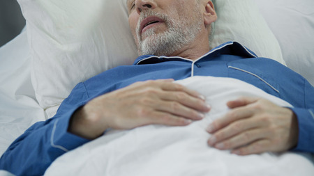 Senior man sleeping in bed and snoring, problems with sleep, health care