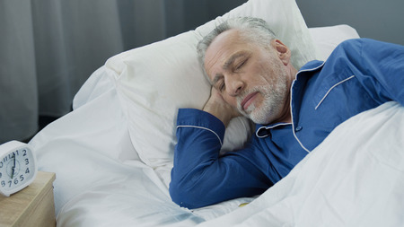 Aged male sleeping in bed in the morning, healthy sleep, recovery time, closeup