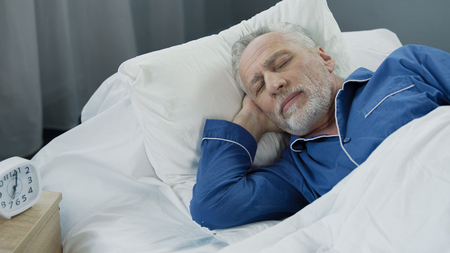 Closeup of retired man sleeping in bed in the morning, recovery time, health