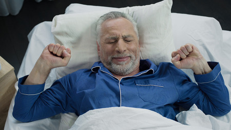 Pensioner stretching in his bed after awakening in the morning, healthy sleep Stock fotó