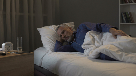 Pensioner impatiently waiting morning to come, suffering insomnia at night Stock Photo