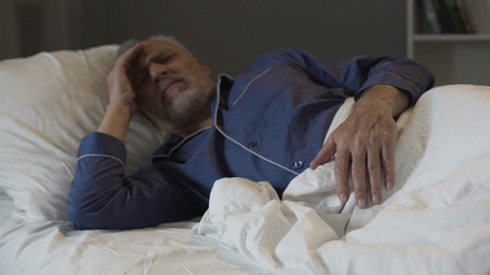 Senior man cannot sleep, suffering terrible headache and migraine, insomnia