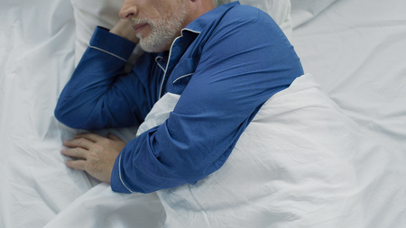 Elder lying in bed, unable to calm down and fall asleep, lack of comfort