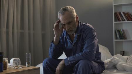 Homem sem dormir sênior, sofrendo de dor de cabeça, sentado no sofá durante a noite Foto de archivo