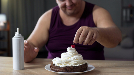 Fat male putting cherry on the top of sweet cake decorated with whipped cream Stock Photo