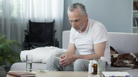 Depressed senior male sitting on sofa at nursing home, loneliness and melancholy
