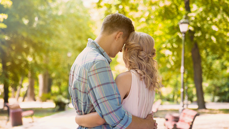 Curly-haired beauty tenderly embracing with handsome boyfriend, tender feelings