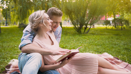 Cheerful couple enjoying leisure in park reading book and having fun together