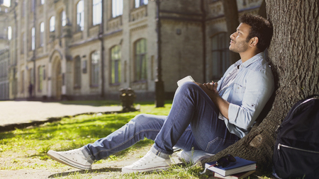 Dreamy young male sitting with notebook under tree, thinking what to write, idea Stock Photo
