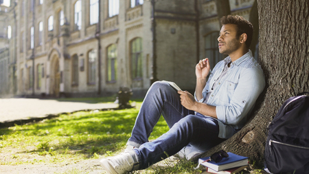 College student sitting with notebook under tree doing home assignment, studying Stock Photo