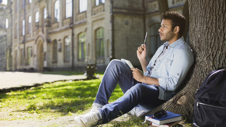 Multinational guy sitting under tree in park writing creative idea in sketchbook