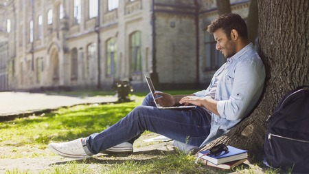 Young mixed-race guy using laptop under tree, smiling at good news, emotions Stock Photo