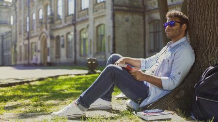 Multiracial man sitting under tree wearing sunglasses, positive mood, energy