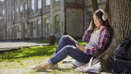 Multiracial girl sitting under tree in headphones, scrolling screen of cellphone