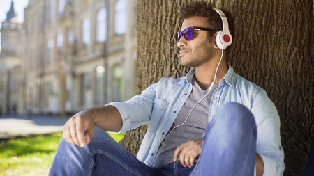 Multiracial guy leaning against tree in headphones and sunglasses, leisure