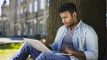 Multiracial college student sitting under tree with laptop, checking final paper Stock Photo