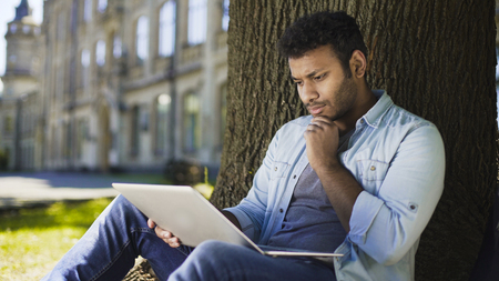 Mixed-race young man sitting under tree, looking at laptop, important letter