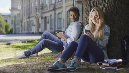 Man with cellphone sitting under tree and looking at girl using phone, affection Stock Photo