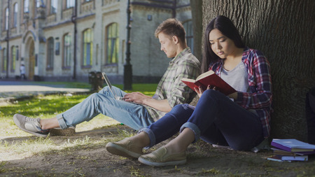 Man with laptop sitting under tree near girl reading book, contemporary youth Stock Photo