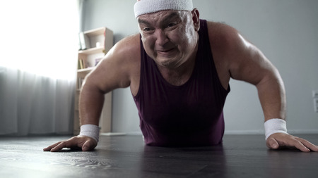 Motivated plump man in his 50s doing push-up with great effort, home training
