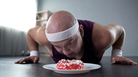 Fat man in sportswear doing push-up and looking at tasty donut in front of him