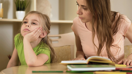 Upset impatient mother making bored daughter to do homework, homeschooling, stock footage Stock Photo