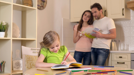 Happy parents proudly watching their smart daughter doing homework, family, stock footage Stock Photo