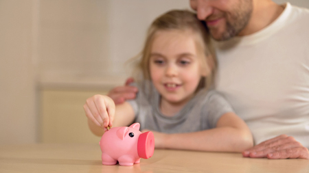 Father teaching little daughter to save money in piggy bank, financial literacy, stock footage