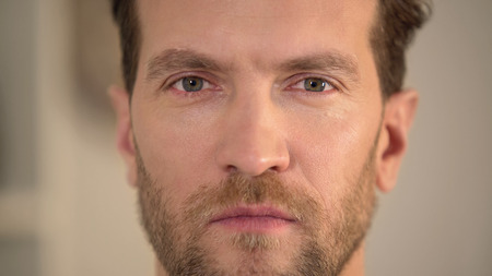 Serious angry man looking into camera, annoyed male face close-up, problems, stock footage