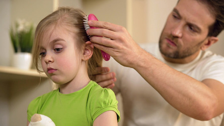 Strict father tenderly combing cute little daughters hair with serious face, stock footage