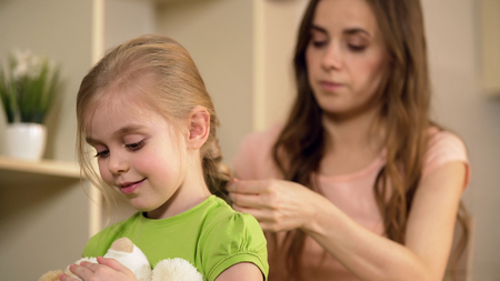 Caring mother braiding happy little daughters hair, taking care of her child, stock footage Stock Photo