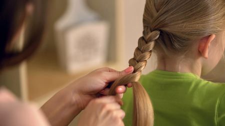 Big sister or babysitter braiding little girls hair, woman taking care of child, stock footage
