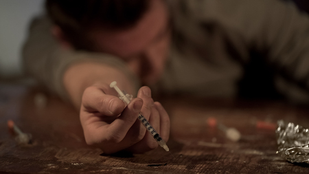 High drug addict lies unconscious after injection, syringe in hand, overdose, stock footage