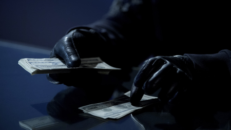 Criminal in black gloves counting bundle of money earned for committing crime, stock footage Фото со стока
