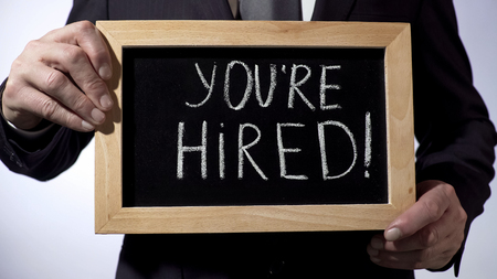 Youre hired with exclamation written on blackboard, businessman holding sign, stock footage