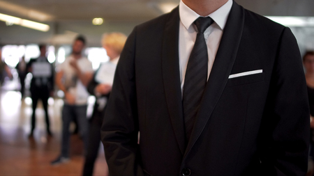 Man in business suit waiting for arrivals in airport hall, travel agent, tourism