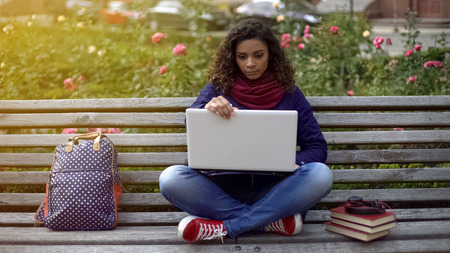 Cute biracial girl carried away by exciting research project, sitting in park