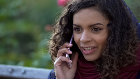 Happy mixed race woman talking over smartphone outdoors, smiling sincerely