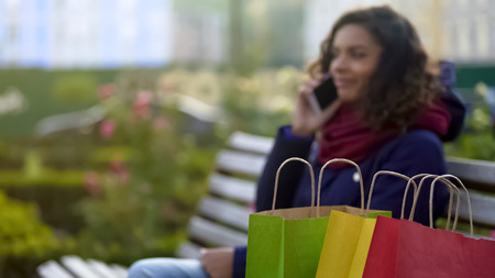 Closeup of shopping bags, woman boasts about purchases over phone on background