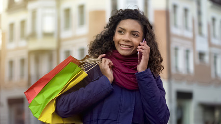Woman with shopping bags calling female friends to tell about discounts in shops