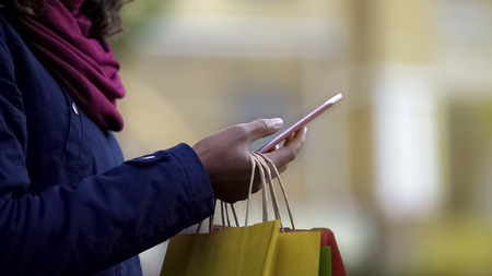 Woman adding desired goods to cart in online store applications, mobile shopping