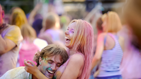 Cheerful couple hugging outdoor festival, having fun together, smiling friends Stock Photo